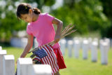 Traylor Elementary first grader Emile Lopez (cq), 7, places a flag in front of a headstone Friday...