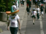 Gary Harding of Weatridge, Co., is protected from the sun by his sombrero as he makes it to mile 3...