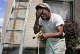 Al Major, cq, owner of Major Painting Company, cools off with a hose while painting a home at 26th...