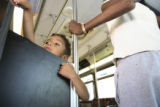 Cain McGory,4, left, watches people come on the bus as Bridgette Daring boards the bus, right. ...