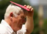 Jaan Raamot (cq), 71, of Broomfield, uses a broshure to shield his head from the sun while waiting...