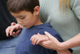 The hands of Teddi Gray, CQ, 45, comfort her nephew Evan Thompson, CQ, 8, in front of their...