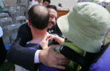 The Mayor of Tel Afar Najim Abdullah (cq), center, gives a hug to Lt. Commander Rich Anderson...
