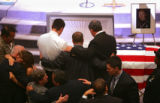 Friends, family and fellow Denver Police officers hug after funeral services for Denver Police...