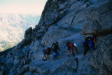 Hikers scramble up the sloping granite of the Ledges section on the Keyhole Route on Longs Peak....