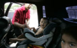 Silvia Soto  buckles in her baby , 2 year old Giavanni, Wednesday afternoon June 21, 2006, after...