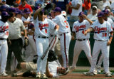 ESPN cameraman Mike Weir is knocked over as Clemson players celebrate a three-run home run by Andy...