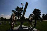 A United States Field Artillery Cannon stands under the American flag at Fairmont Cemetery,...