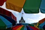 An American flag is seen through colorful umbrellas at Heritage Square in Golden, CO, Sunday...