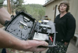 Shaffer Warner (cq) holds a camera with motion sensors that he bought to try and catch images of...