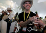 Moet Hennessy brand manager Alberto Dias, cq, serves champagne in the Grand Tasting Tent during...