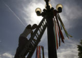 People's Fair volunteer Jeramy Nydam (cq) hangs a windsock from a light fixture in Civic Center...