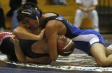 Joshua Starr (in blue) of Grandview puts the hurt on  Eaglecrest's Wayne Stafford and Starr won at...