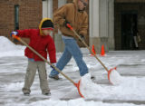 Adolfo Sosa, left, 4 years old, was helping his dad, Martin Soas (cq), remove snow from the...