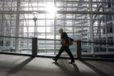 Secretary of State Mike Coffman walks across a skybridge inside 1700 Broadway as officials from...