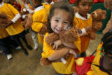 Preschooler, Breanna Romero, cq, 3 years-old, hugs a teddy bear she just received, Wednesday Dec....