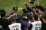 (Denver shot on 4/4/05) The Colorado Rockies swarm short stop Clint Barmes after he hit a two run...
