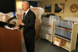 Mike Coffman, Colorado Secretary of State, stands in front of boxes and binders during the press...