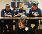 Alicia Blowers, bottom, sits beneath a table as  Steelworkers from left-Steve Miller, Lori...