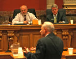 Colorado Secretary of State Mike Coffman (front) talks to Senator Ken Gordon, left, and State...