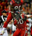 Houston Texans #90, Mario Williams does a hula dance as teammate #96, Anthony Weaver, top, jumps...