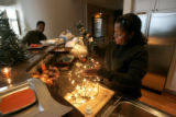 0126 Partners Nita Mosby-Henry, left, and Carla Harvard celebrate Christmas while putting up a...