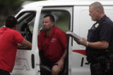 Safelite AutoGlass employees talk with Denver Police after their vehicle was struck by a bank...