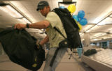 Sean Swarner, two-time cancer survivor and Colorado resident, unloads one of his two bags for the...