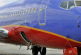 A Southwest Airline luggage handler situates baggage in the undercarriage of a Southwest Airline...