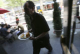 Ben Mohammed, (cq) a server, moves through the patio adjusting customer requests during the busy...
