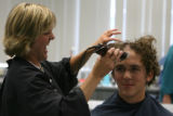 Rachele Graham, cq, laughs as she cuts the hair of Joshua Johnson, cq, of Seattle, Washington,...