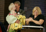 Rich, holding daughter Lizzie, and Liesel Von Duyke, holding Rich's hand, fight back tears as they...