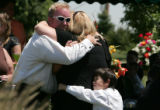Liesel Von Duyke , back to camera is comforted by a man and his son at graveside services for her...