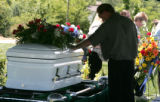 Rich Von Duyke, touches the casket of his 8 year old son Quinton Von Duyke, after graveside...