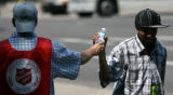 Kerry Kenny, cq, of The Salvation Army, hands a bottle of water to a passer by Alfredo Zuniga, cq,...