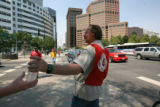 Ray Christenson, cq, of The Salvation Army, hands out water to a passer by (how didn't want to be...