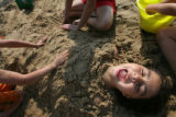 9 year-old Page Espinoza (cq) gets buried in sand by her friends 12 year-old Kaila Griffin (cq), 6...