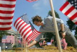 Alexander Konetzki (cq), 25, of Chicago, places flags on the stage before a campaign event for...