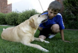 Caleb Seeton(cq), 12, gets a kiss from Ute, a six-year-old golden retriever, outside of his...