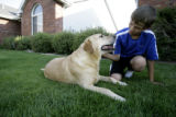 Caleb Seeton(cq), 12, plays with Ute, a six-year-old golden retriever, outside of his Windsor home...