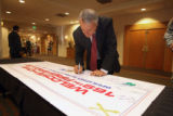 Gov. Bill Ritter (cq) signs a welcome home banner for  members of the 169th Fires Brigade Colorado...