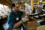 Shift manager, Billy Bindewald, cq, of Sunflower Markets, bags a customers groceries Tuesday July...