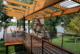 The new wood deck, with a pergola design on top, extends from the back of the house, with a nice...