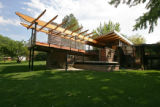 A new wood deck, with a pergola design for a roof, extends from the back of the house, with a nice...