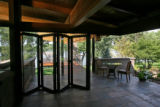 Glass folding doors can open or close, which can make the solarium, with no walls on two sides, on...