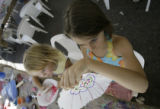 Chana Hancox, 7, looks at her artwork that will be made into a flower as her sister, Charlotte, 4,...