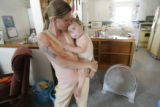 070 Stephanie Lords, 33, or Wray, Colo., holds her youngest daughter Alysa Lords, one, in their...