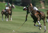 Marcelo Freyre leans out to strike the ball in the first match at the 20th Annual Denver Polo...