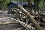 DLM0116  Mangled and twisted trees, downed by a mudslide, are strewn around a garage  in the...