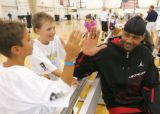Tony Romero (cq), 9, of Hollywood, Calif., slaps hands with Nuggets star Carmelo Anthony during...